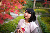 Young woman looking at red autumn leaves