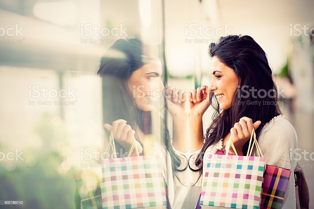 Young woman looking at shop window stock photo