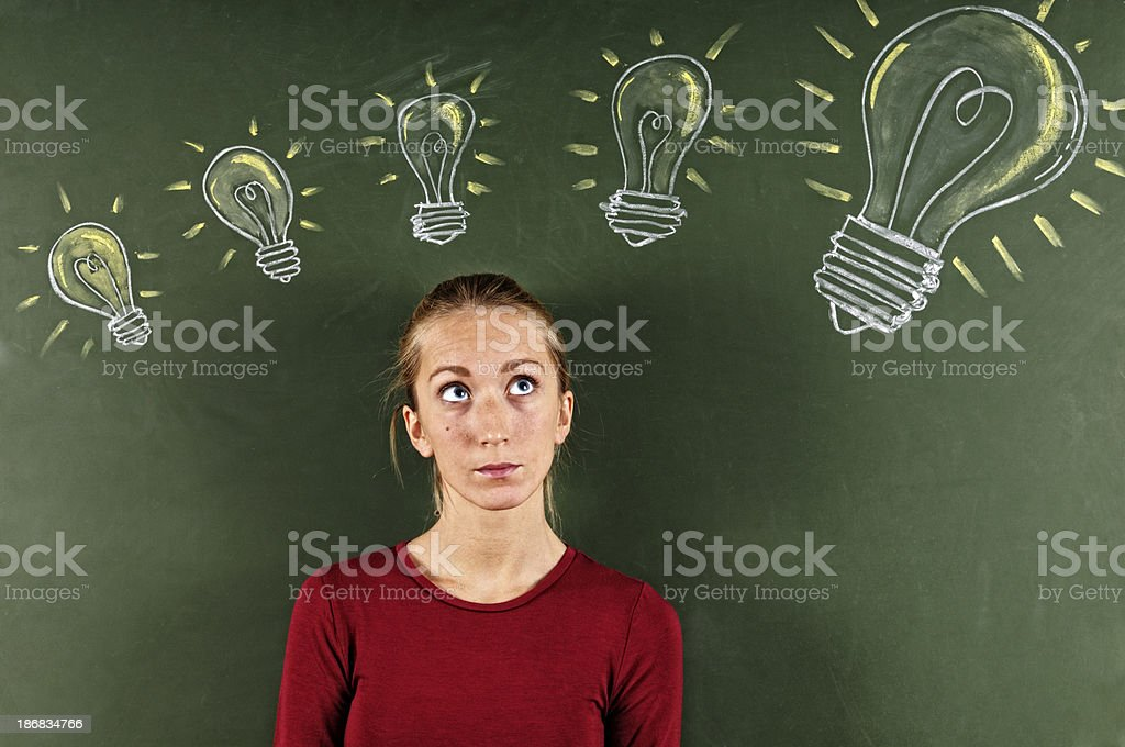Young Woman Looking at Sketched Light Bulbs royalty-free stock photo