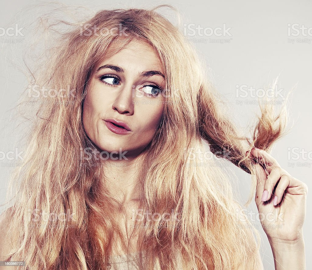Young woman looking at split ends stock photo
