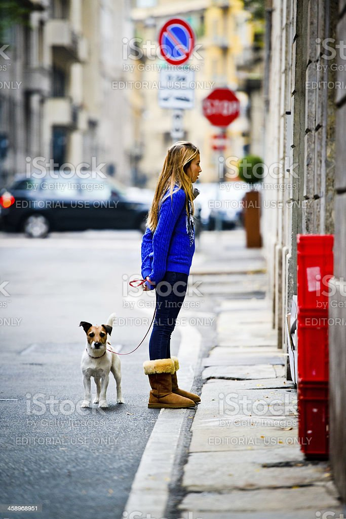 Young Woman looking at Store Window Display while walking dog royalty-free stock photo
