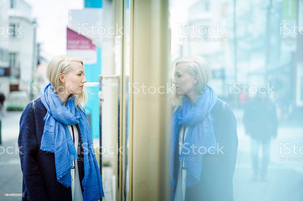 Young woman looking at store window stock photo