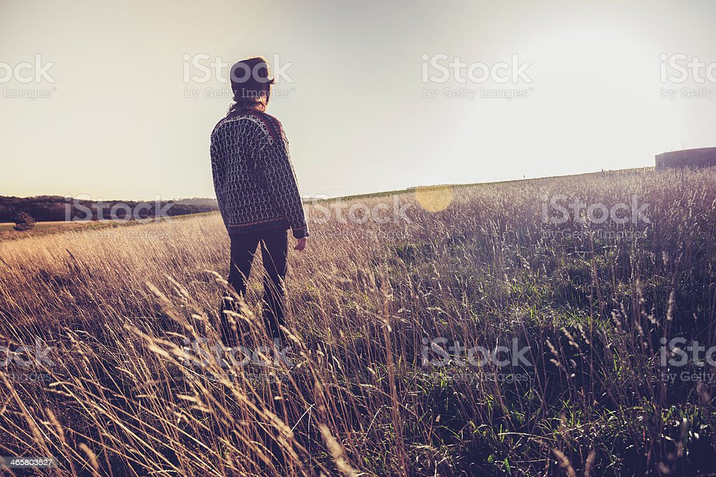 Young woman looking at sunset in meadow stock photo