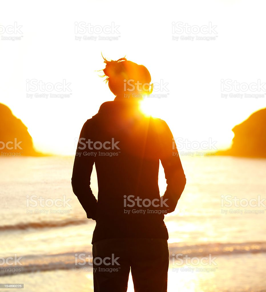 Young woman looking at sunset stock photo
