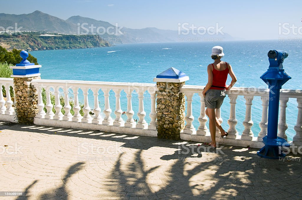 Young woman looking at the sea in Nerja stock photo