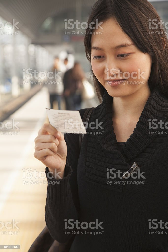 Young Woman Looking At Train Ticket on Railroad Platform royalty-free stock photo