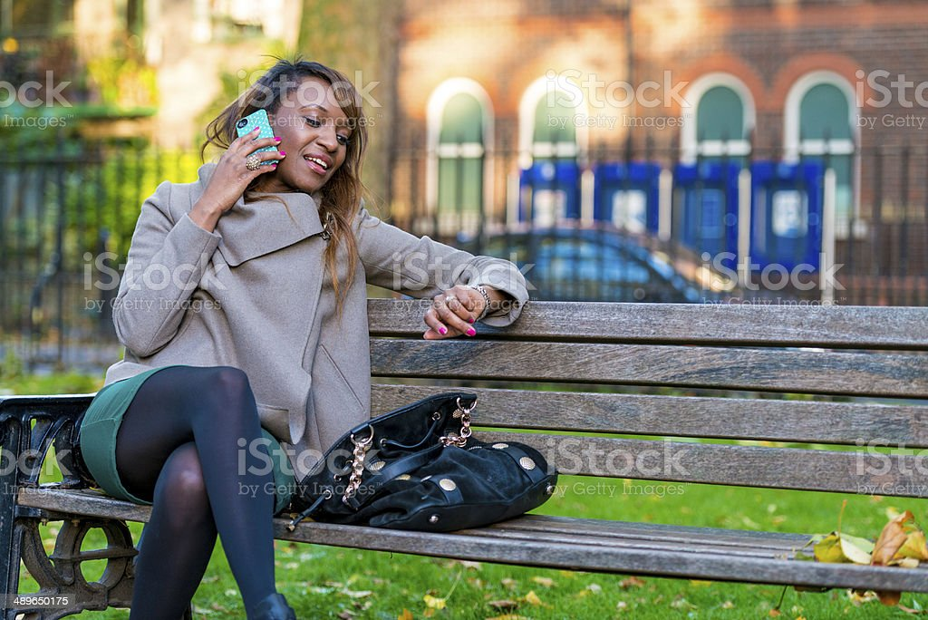 Young woman looking at watch while on the phone. royalty-free stock photo