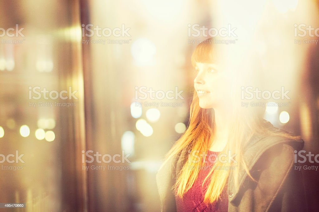 Young woman looking at window store stock photo