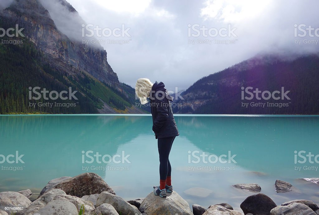 Young woman looking away from camera at turquoise Lake Lousie stock photo