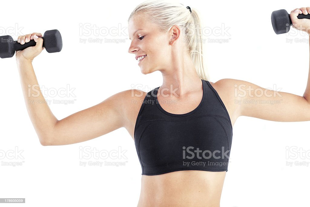 young woman looking away while lifting dumbbell stock photo