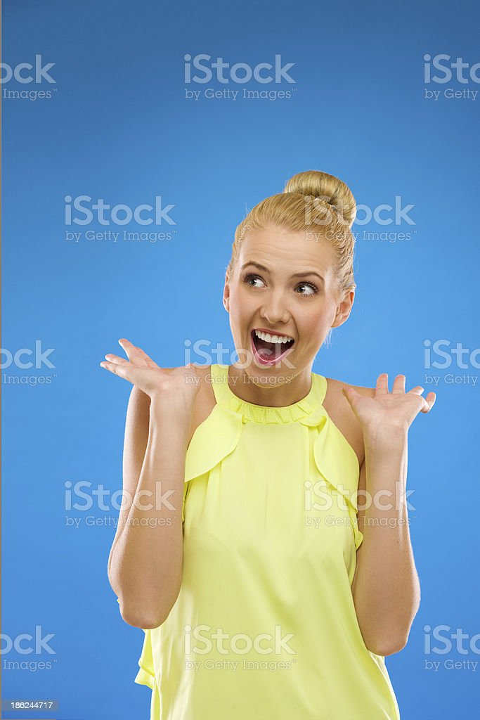 Young woman looking excited against blue background. stock photo