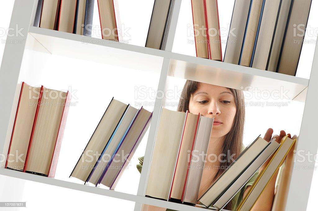 Jeune femme à la recherche d'un livre photo libre de droits