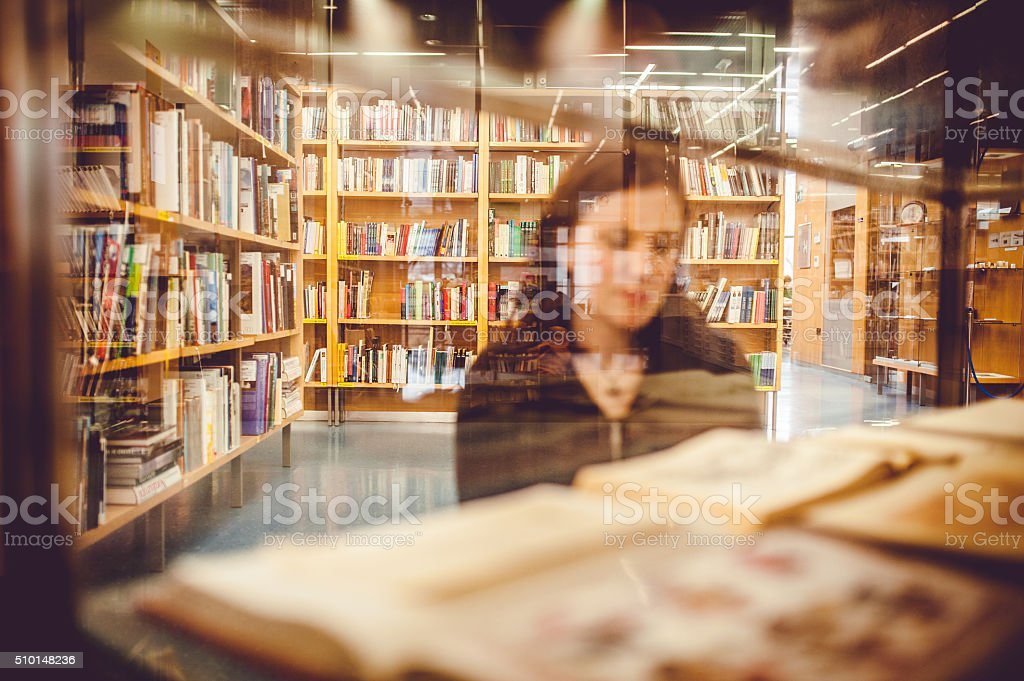 Young Woman Looking for Books in Public Library stock photo