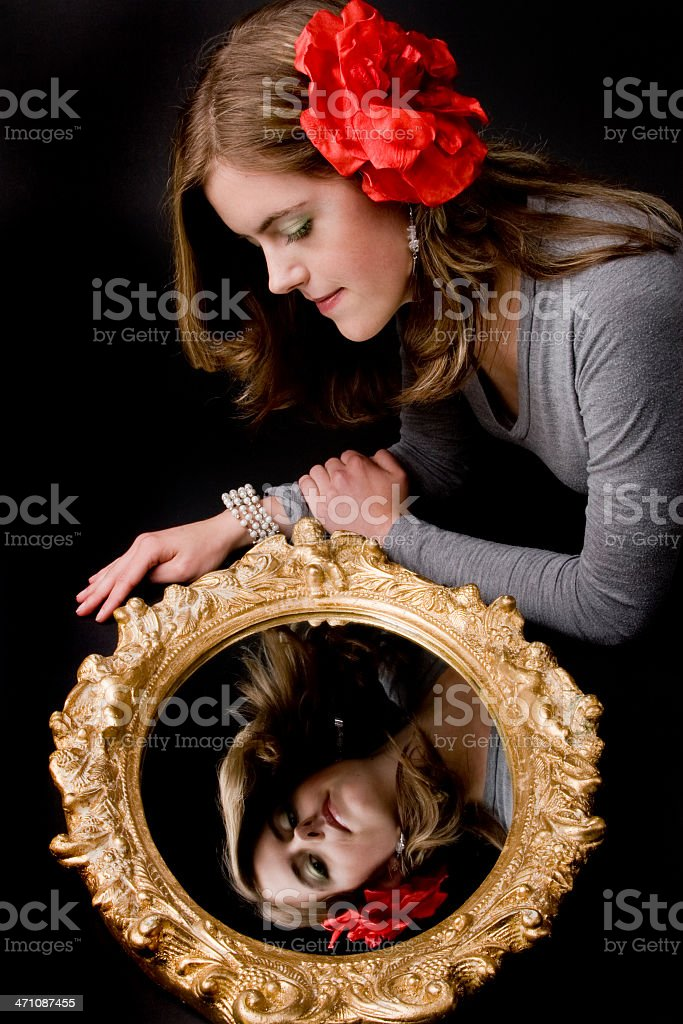 Young woman looking in mirror royalty-free stock photo