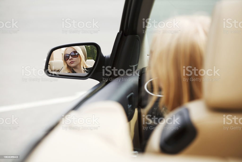 Young woman looking in the car mirror royalty-free stock photo