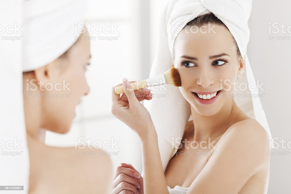 Young woman looking in the mirror and putting make-up on royalty-free stock photo