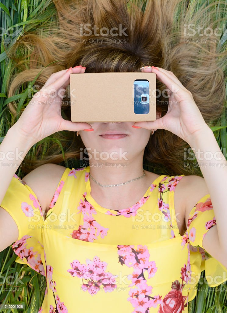 Young woman looking into a virtual reality glasses stock photo