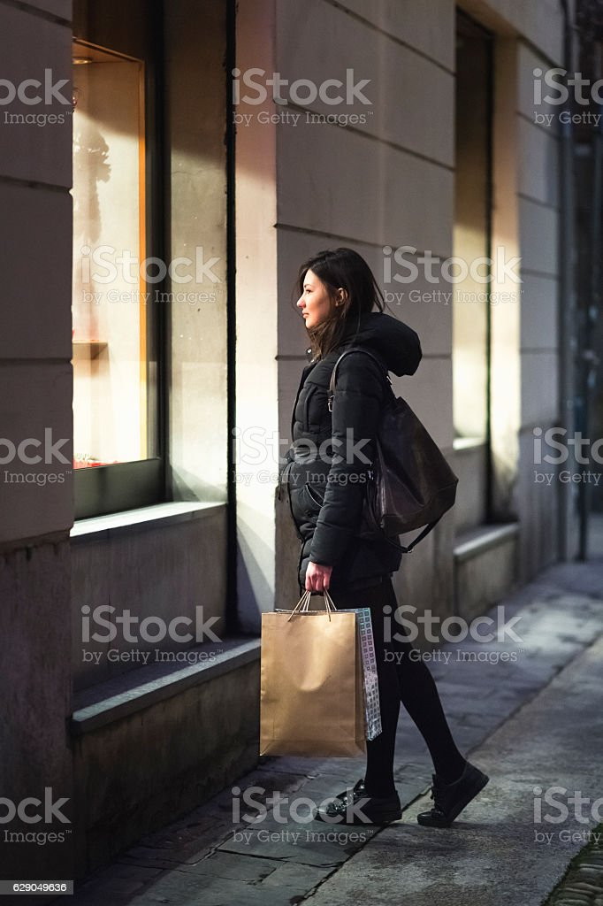 Young woman looking into shopwindow. stock photo