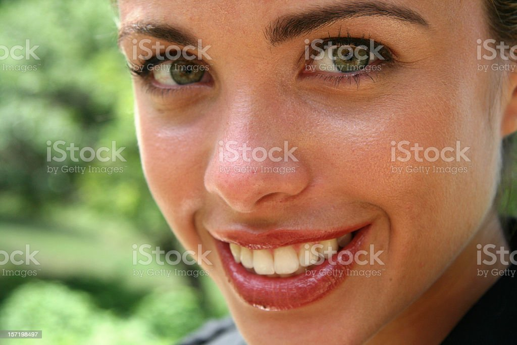 A young woman looking into the camera and smiling. stock photo