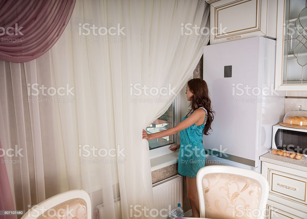 Young Woman Looking Out Kitchen Window stock photo