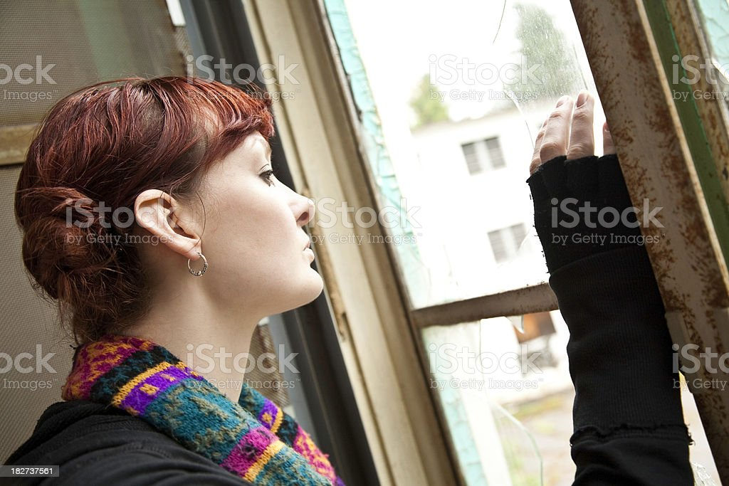 Young Woman Looking Out of Broken Window royalty-free stock photo