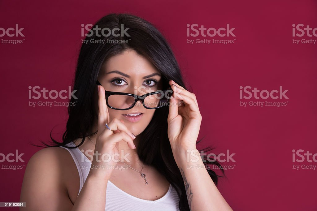 Young woman looking over glasses with slight smile. stock photo