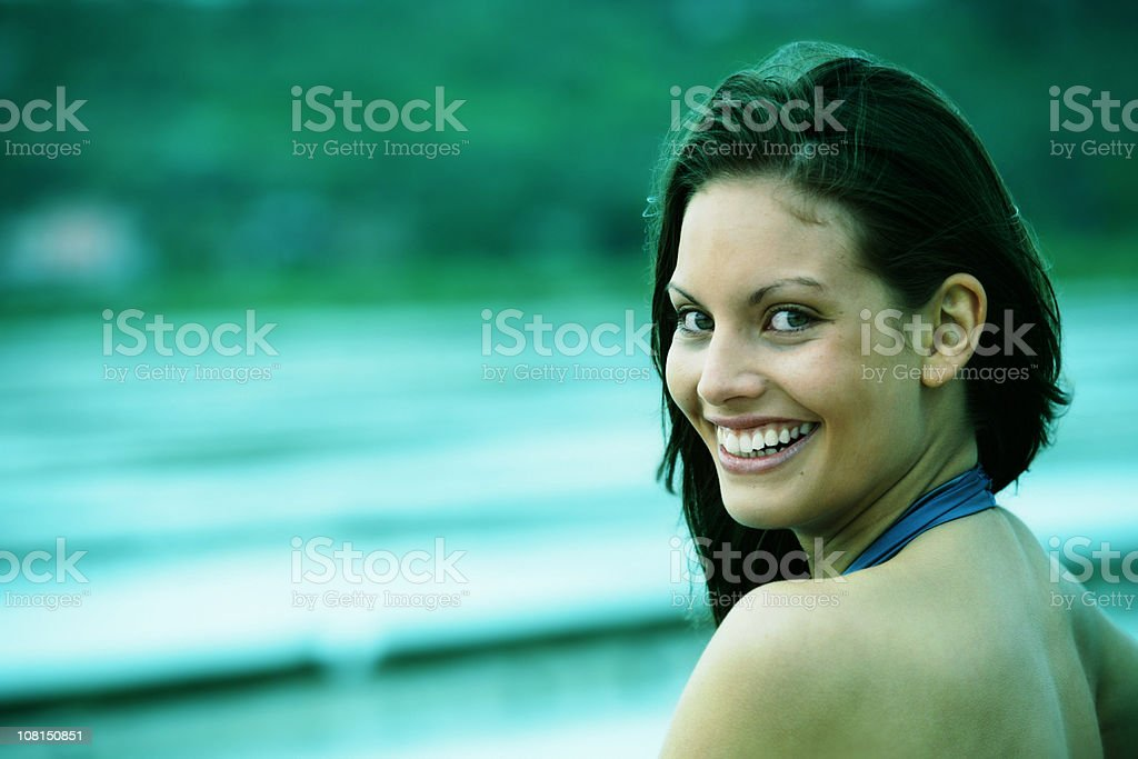 Young Woman Looking Over Shoulder and Smiling stock photo