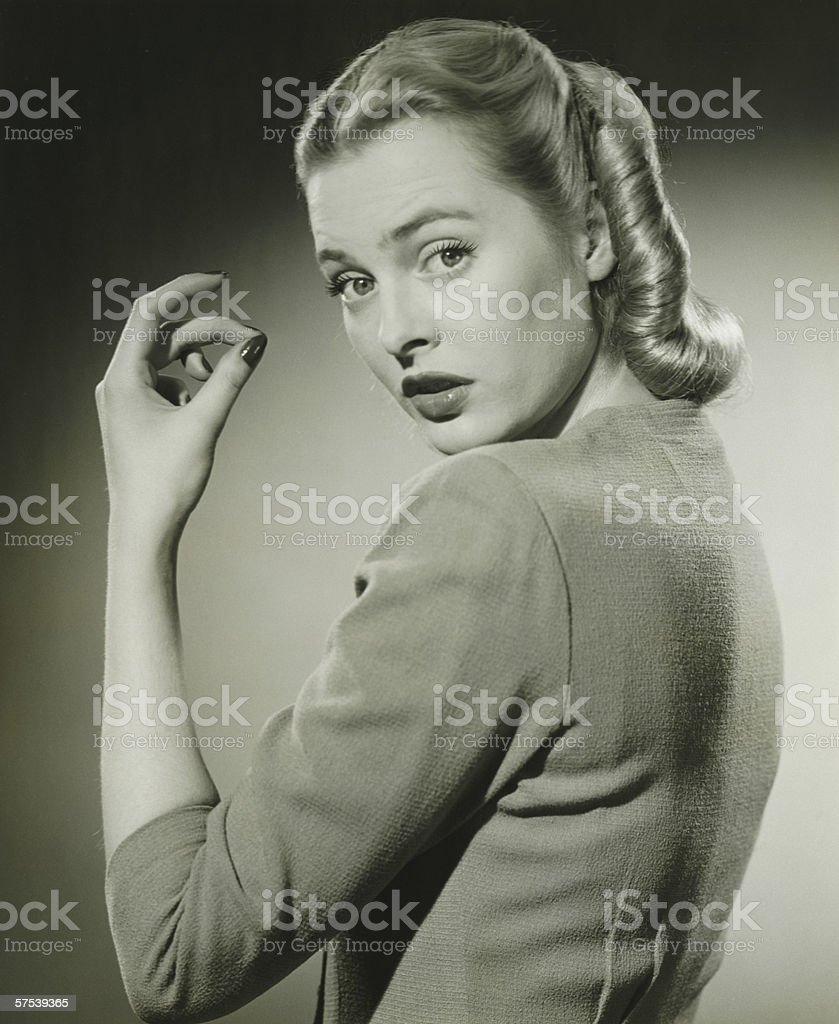 Young woman looking over shoulder, (B&W), portrait royalty-free stock photo