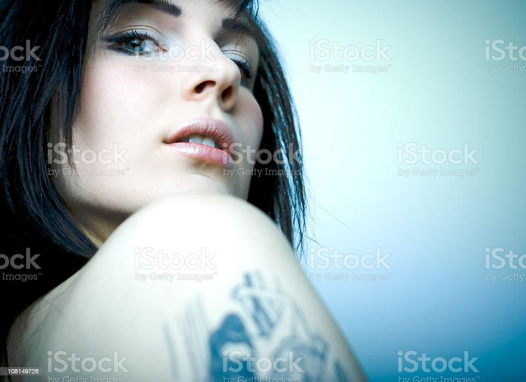 Young Woman Looking Over Shoulder with Tattoo royalty-free stock photo