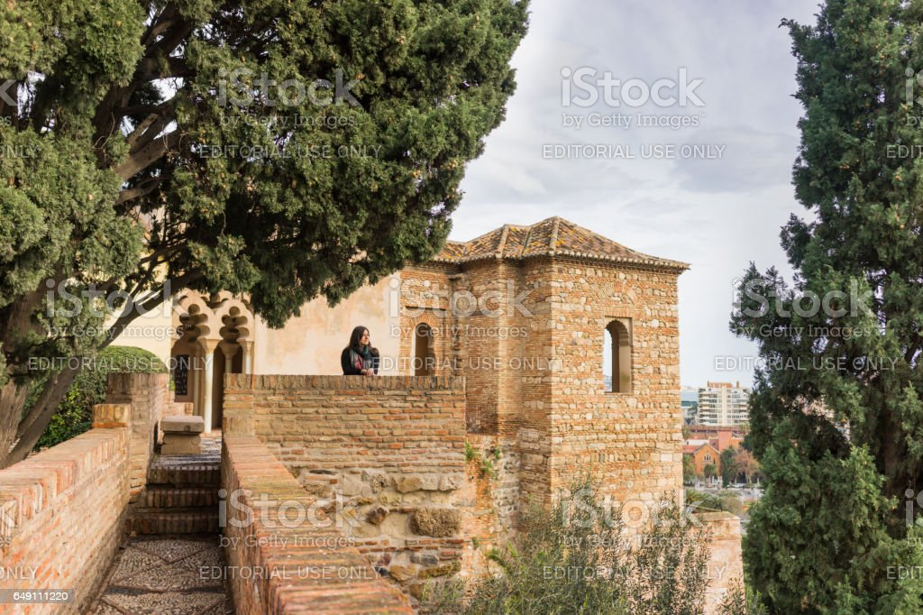 Young woman looking over the city of Malaga, Spain from the walls and towers of an ancient medieval Alcazaba fortress. Beautiful castle architecture with arches and trees on a sunny day. stock photo