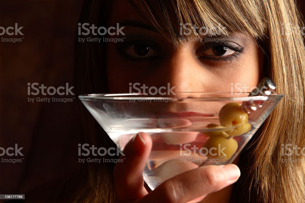 Young Woman Looking Over Top of Martini Drink stock photo