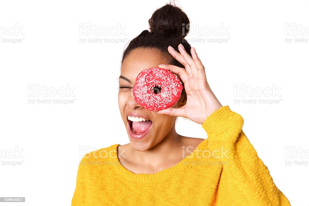 Young woman looking through a donut stock photo