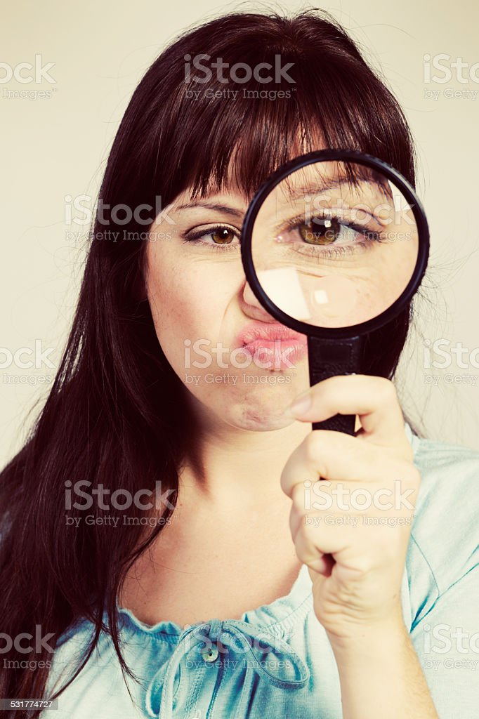 Young woman looking through magnifying glass scowls grumpily stock photo