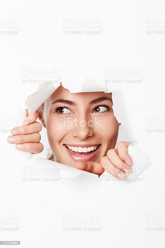 Young woman looking through ripped hole in paper stock photo