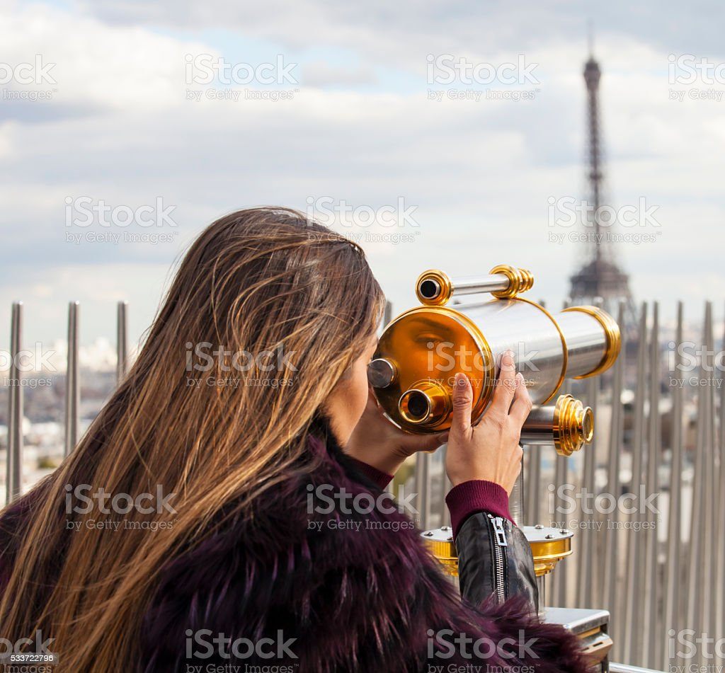 Young woman looking through telescope to Eiffel tower stock photo