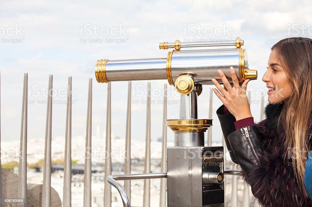 Young woman looking through telescope-side view stock photo