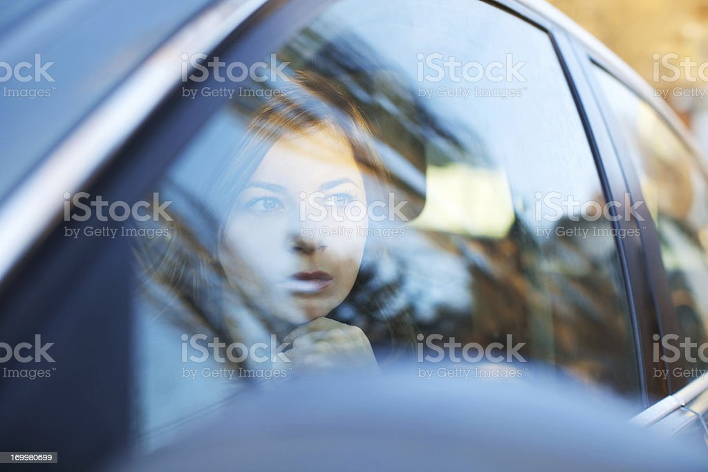 Young woman looking through the car window stock photo