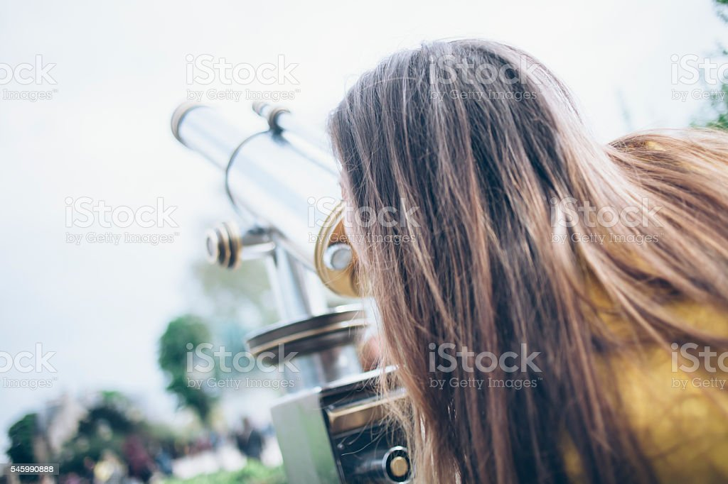 Young woman looking through tourist telescope stock photo