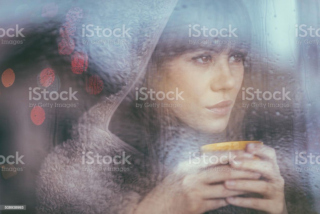 Young woman looking through window on rainy day stock photo