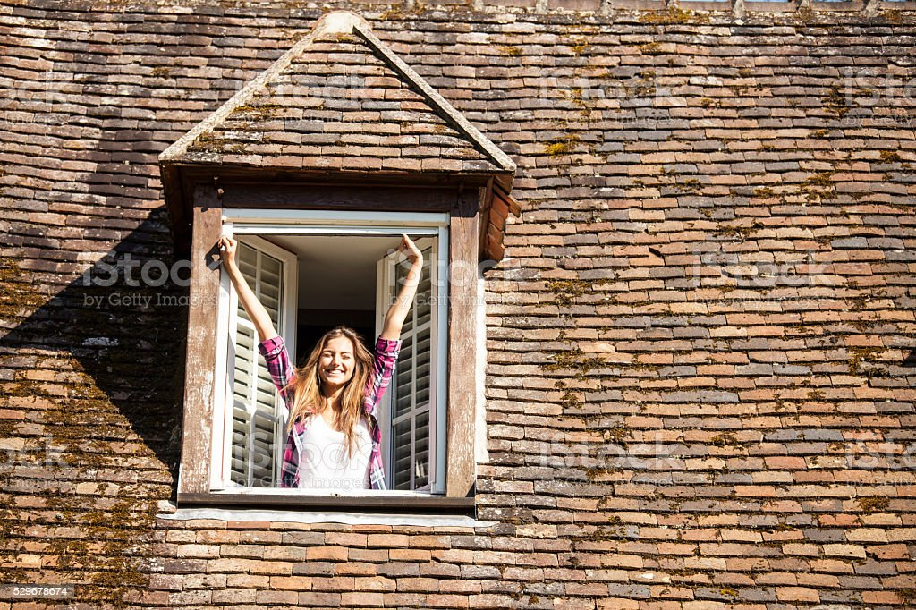 Young woman looking through window stock photo
