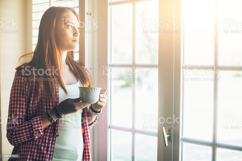 Young woman drinking tea and looking through window. With long hair...