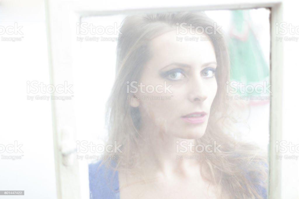 beautiful young woman looking through window
