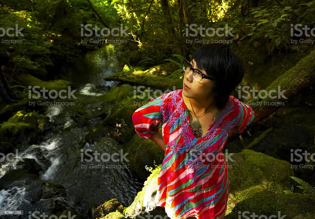 Young woman looking up in forest stock photo