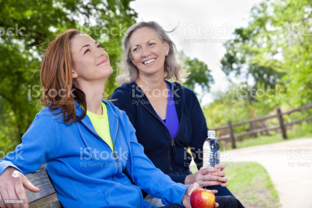 Young Woman Looking Up To Sky With Friend at Park royalty-free stock photo