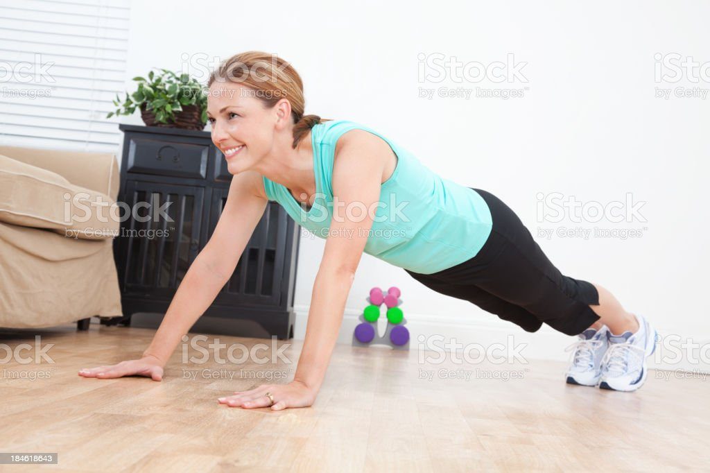 Young woman looking up while doing push-ups in living room royalty-free stock photo