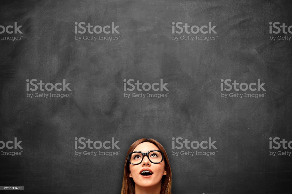 Young woman looking up with blackboard stock photo
