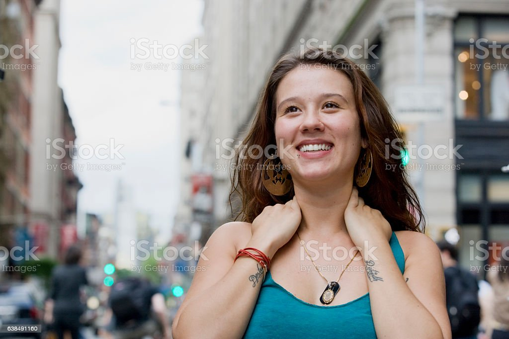 Young woman looking upward in downtown city stock photo