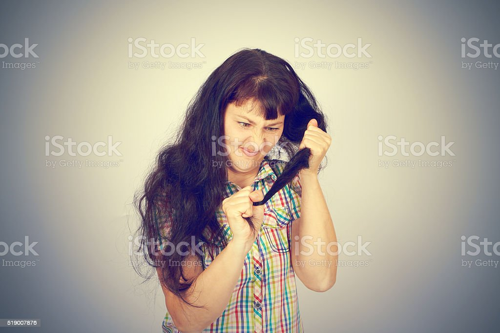young woman looks at her problematic hair stock photo