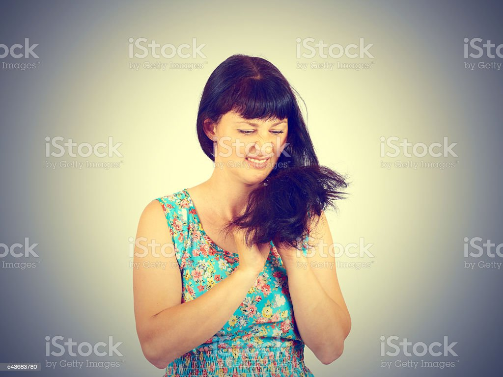 young woman looks at her problematic hairs. stock photo