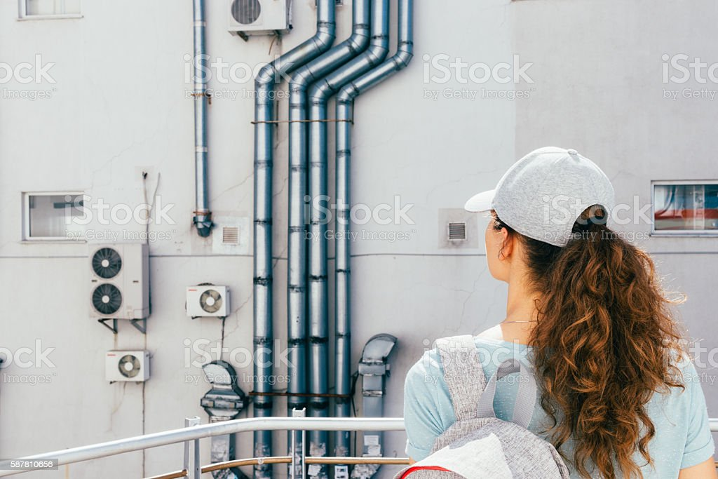 Young woman looks at the wall of the building stock photo